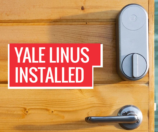 Silver Yale Linus Smart Lock Installed On Wooden Door
